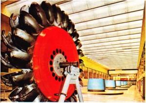 Bir hidroelektrik santralda makine odası, ön planda bir pelton türbinin çarkı görülüyor.
